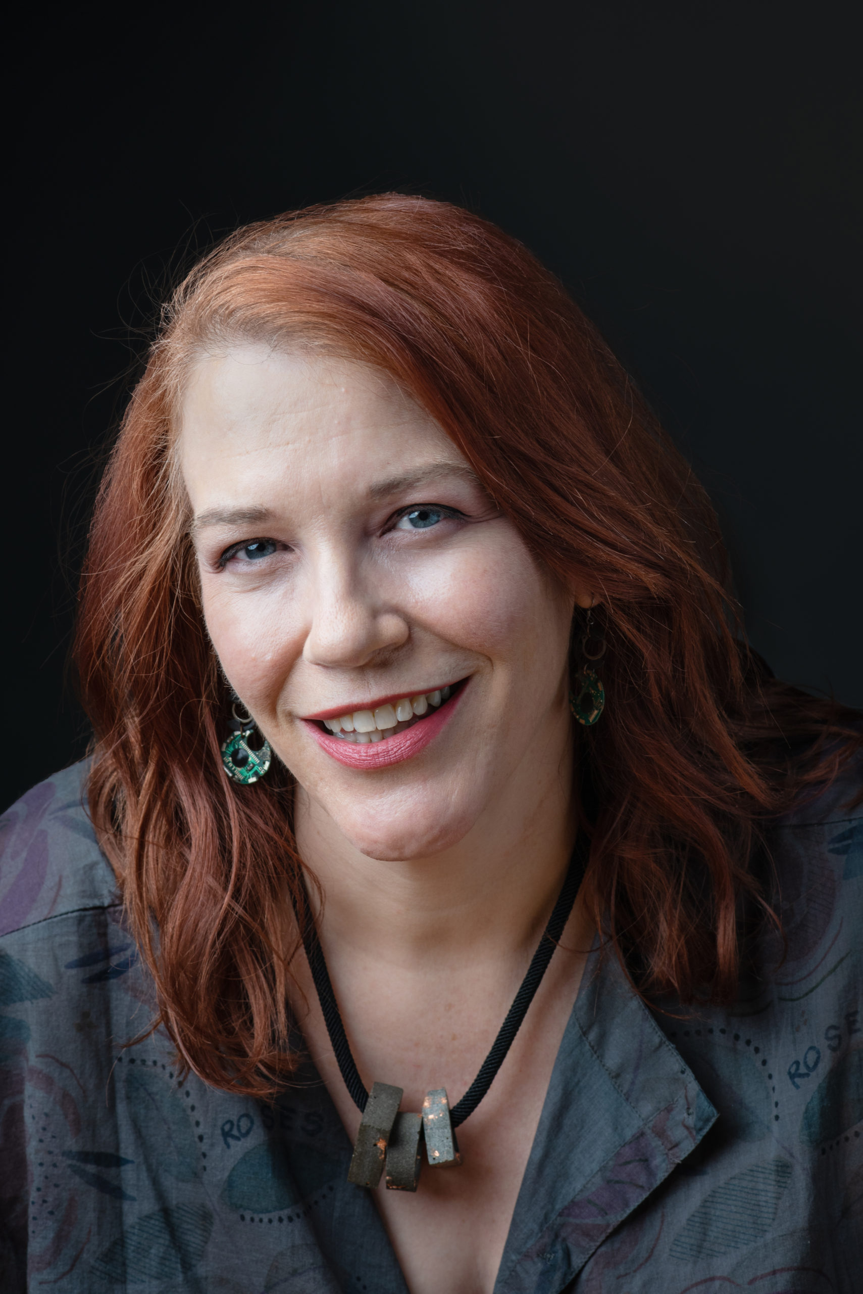 Image shows writer Kelly Robson, smiling, with red hair